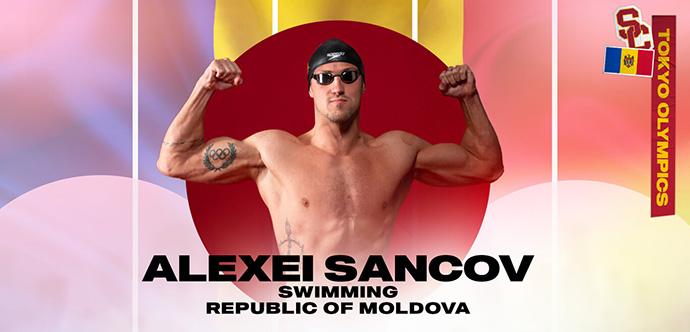 Aleksejs Sankovs nēsā peldcepuri un brilles, rokas sakrustojis sarkanā aplī, un uz Moldovas Republikas karoga fona ir uzrakstīts viņa vārds, sporta specialitāte un valsts.