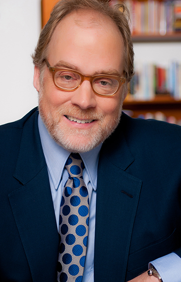 Portrait of Mike Murphy with glasses, dark blue suit coat, light blue shirt and gray tie with blue dots